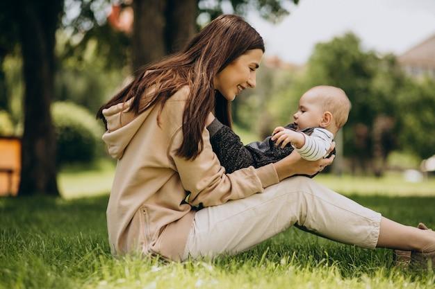 草の上に座って公園で彼女の幼い息子を持つ母