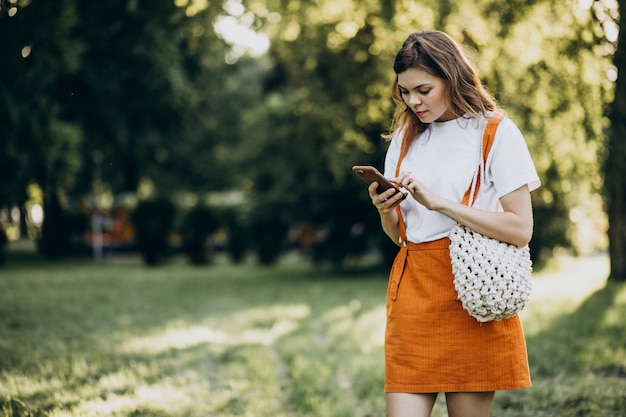 公園で電話で話している若い女性