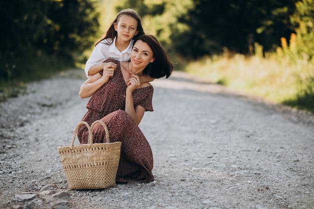 Молодая мать с дочерью идет по дороге в лесу