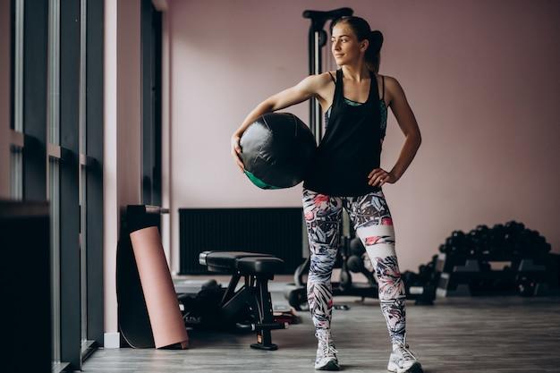重量でジムで運動若い女性