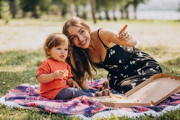 小さな男の子を持つ若い美しい母親が公園でピザを食べる