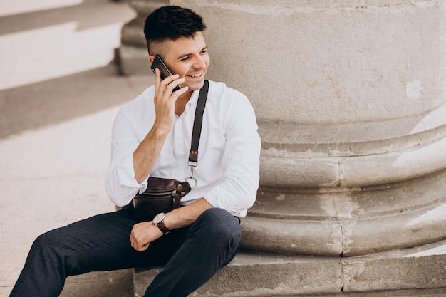 大学で電話を使用してビジネスの男性