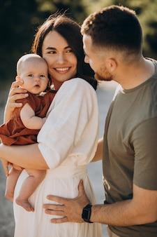 Молодая пара с маленькой дочкой в парке