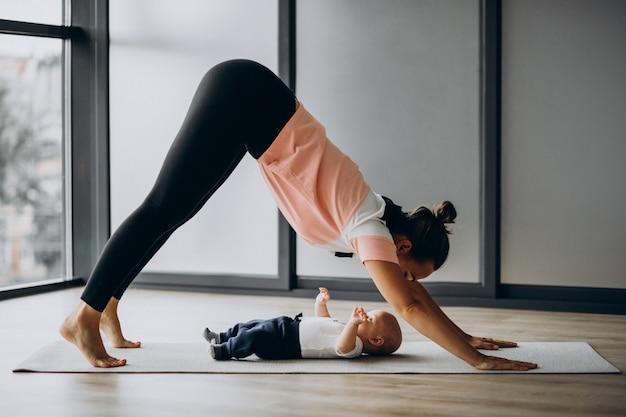 小さな男の子のヨガの練習を持つ母
