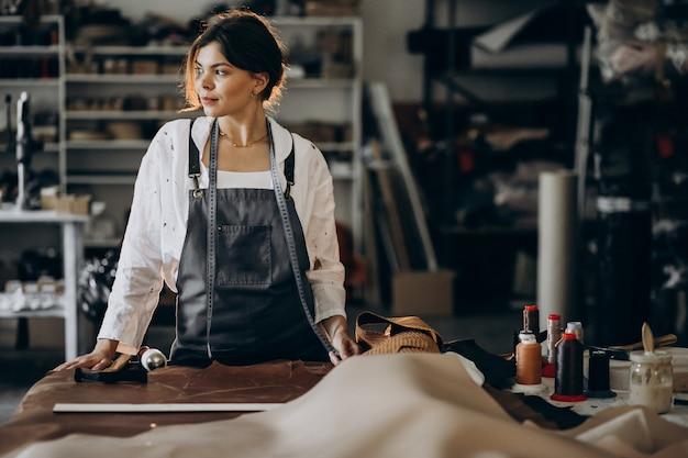 革の生地に取り組んでいる女性のテーラー