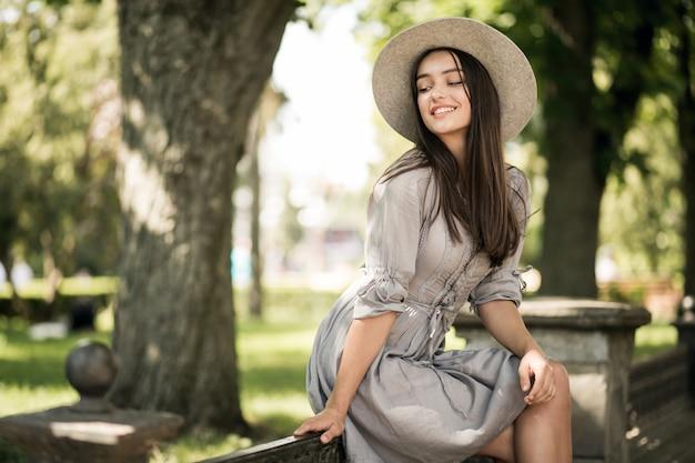 女の子の街の帽子の携帯電話の移動