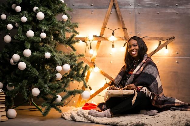 アフロアメリカ人女性がクリスマスプレゼントを開梱