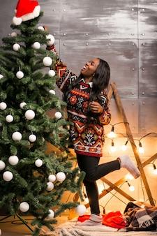 アフロアメリカの女性、クリスマスツリーでおもちゃを吊るす