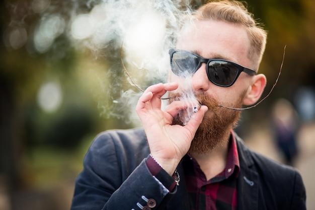 Бородатый человек курит