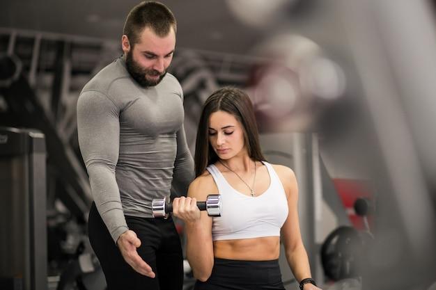 Женщина в тренажерном зале с тренером
