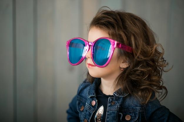 Маленькая девочка в больших солнцезащитных очках