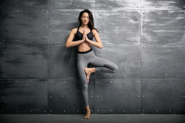 Девушка в тренажерном зале делает йогу