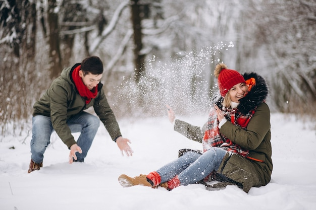 冬に雪の中で遊んでいるカップル