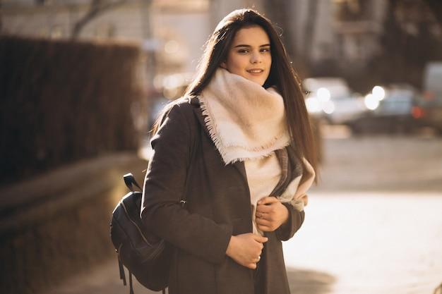 通りの中のコートとスクラフの女性