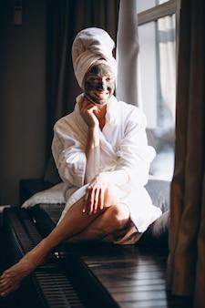 Женщина с черной маской на лице в халате