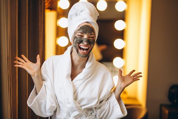 Женщина с черной маской на лице в халате в ванной комнате