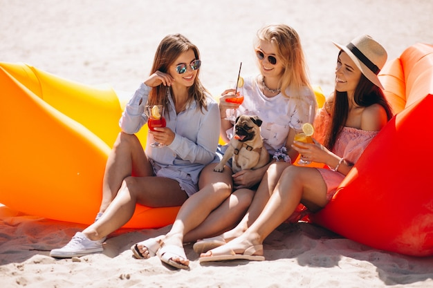 Девушки друзья с коктейлями, сидящими на матрасе бассейна