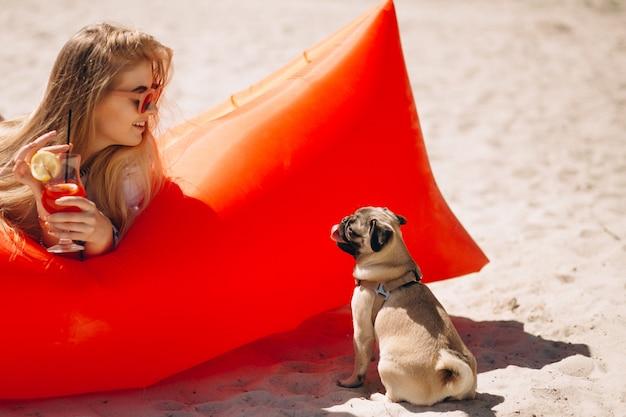 Женщина с коктейлем, лежащим на бассейне матрас на пляже