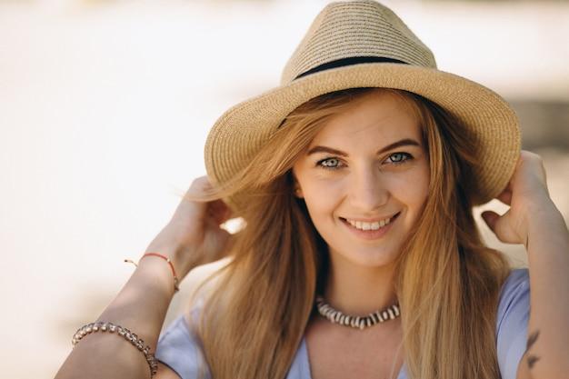 Женщина счастлива в шляпе на пляже