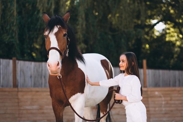 牧場で馬を持つかわいい女の子
