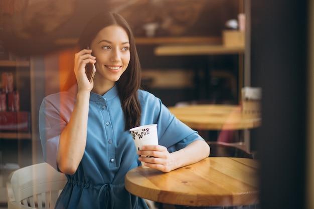 Деловая женщина с кофе и говорить по телефону в кафе