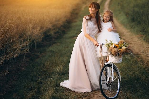 彼女の子供と母、自転車付きの美しいドレスで
