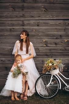 自転車で美しいドレスを着た娘と母