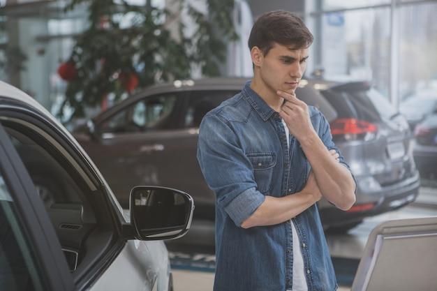 Красивый мужчина выбирает новый автомобиль для покупки