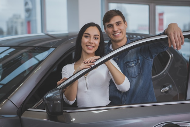 Счастливая пара покупает новую машину в салоне автосалона