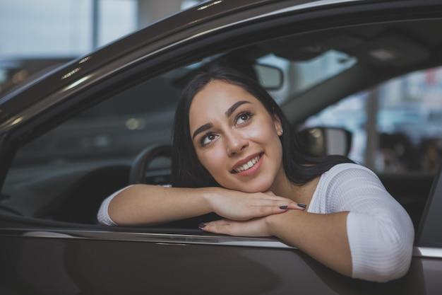Прекрасная молодая женщина покупает новую машину в автосалоне