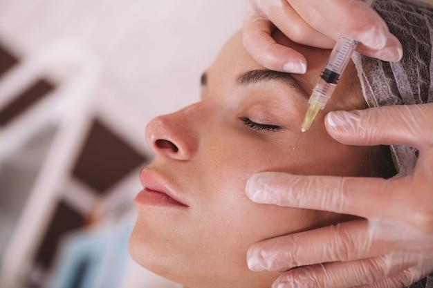 Женщина получает инъекции филлеров в клинике красоты
