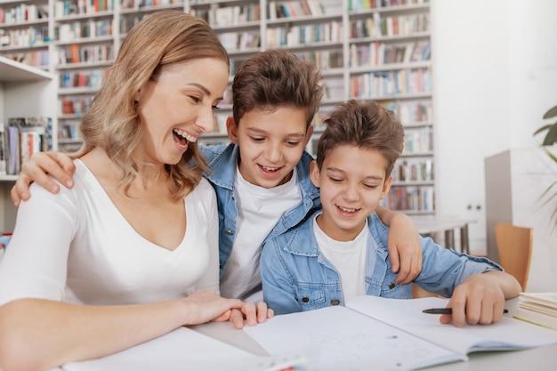 Взволнованная женщина смеется со своими детьми, помогая им с домашней работой в библиотеке