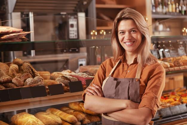 彼女のパン屋で働いている成熟した女性のパン屋