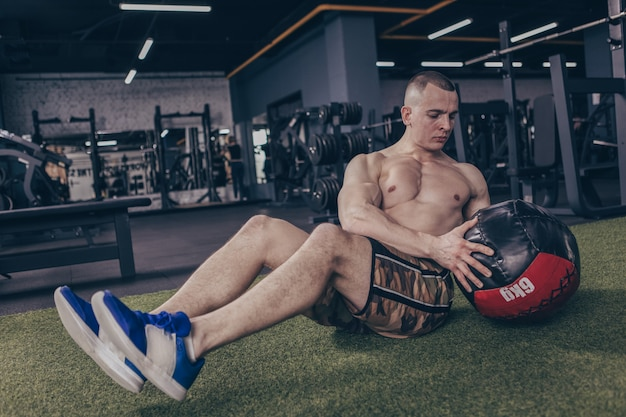 Спортсмен без рубашки работает с мячом медицины