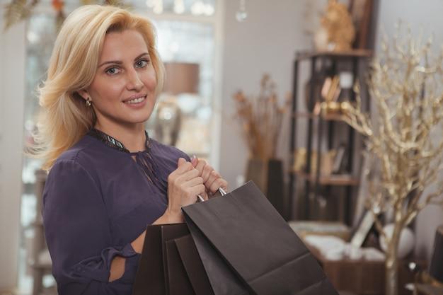 Великолепная зрелая женщина, делающая покупки в магазине домашнего декора