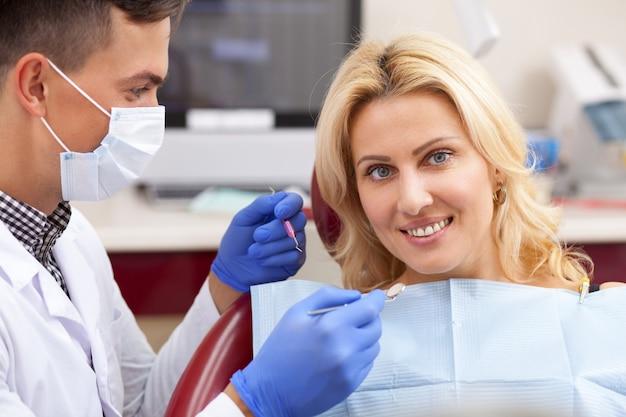 健康的な完璧な歯笑顔、歯科用椅子に座って美しい幸せな成熟した女性。