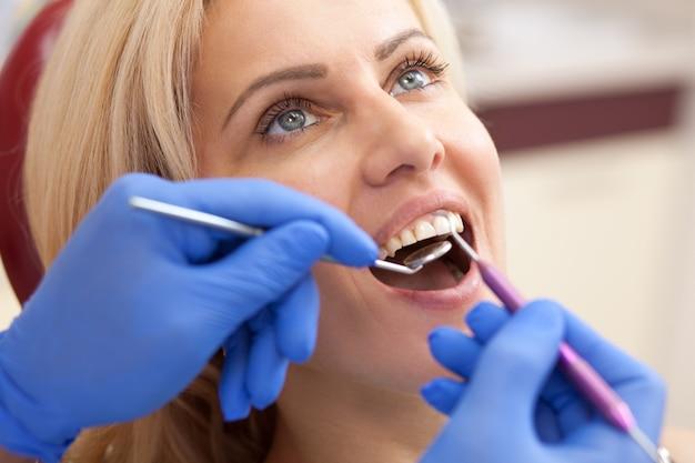 プロの歯科医による歯の検査を受けた美しい成熟した女性のトリミングショットを閉じます。
