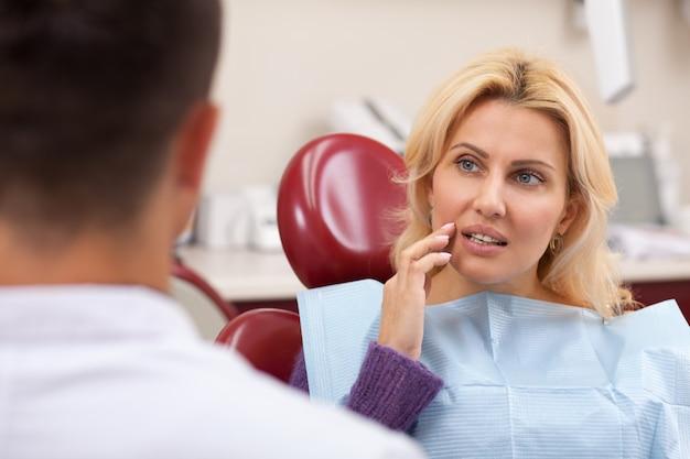 彼女の歯痛の治療を受ける前に彼女の歯科医に話している豪華な成熟した女性
