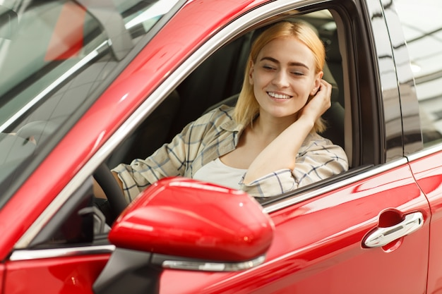 ゴージャスな女性が彼女の車に座って、サイドミラーで見ている彼女の髪を修正します。