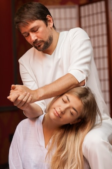 スパセンターで働いている彼の女性のクライアントの首を伸ばしている成熟した男性のタイのマッサージ師の垂直ショット。伝統的なタイ式マッサージを楽しむ魅力的な女性。指圧、癒し
