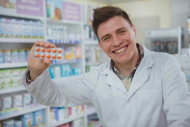 彼のドラッグストアで働いているハンサムな男性薬剤師