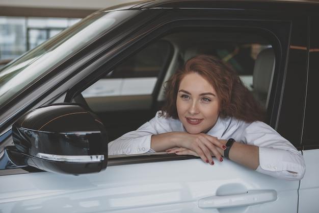 Шикарная женщина покупает новую машину в автосалоне