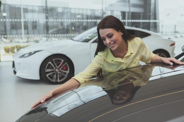 ディーラーで新しい車を買うエレガントな若い女性