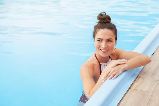 スイミングプールでリラックスした豪華な女性
