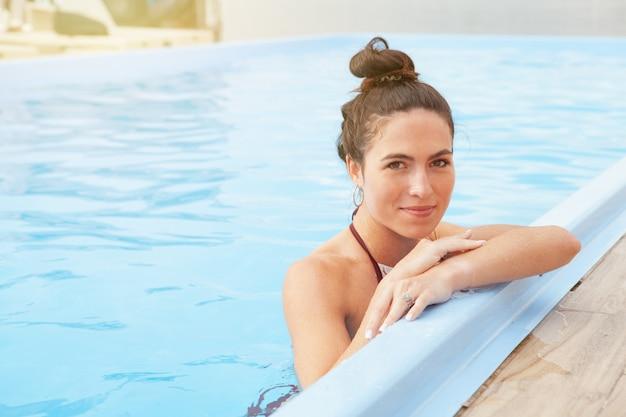 Великолепная женщина расслабиться в бассейне