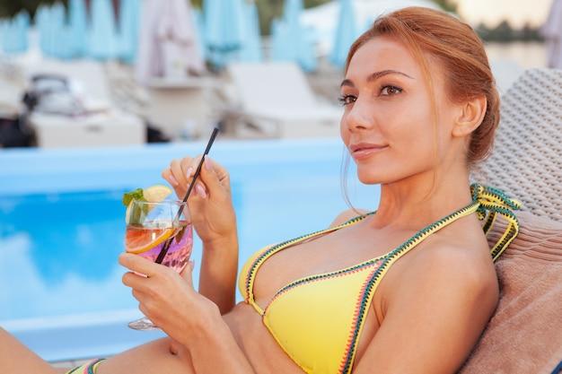 ホテルのプールサイドでリラックスした幸せな健康な女性