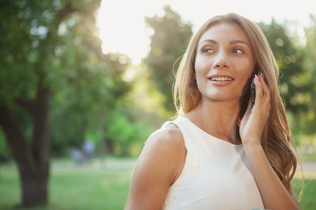 屋外の電話で話している美しい女性