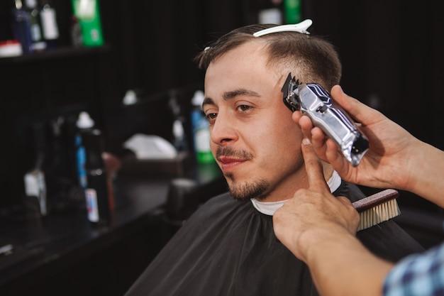 理髪店で新しい散髪を取得する成熟した男