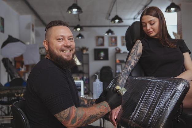 Молодая привлекательная женщина получает новую татуировку от профессионального татуировщика