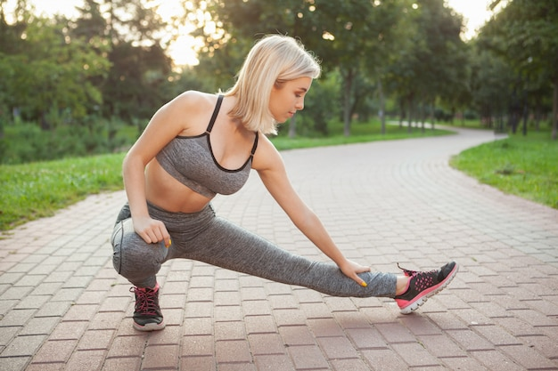 Очаровательная молодая спортсменка тренируется в парке по утрам
